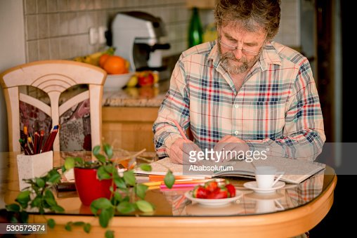 Senior Man with Beard Coloring Book and Having Coffee,  Europe