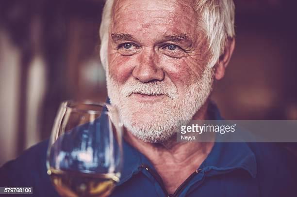 Senior homme avec barbe boire un verre de vin blanc