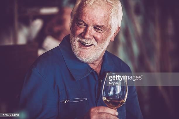 Alter Mann mit Bart trinkt ein Glas Weißwein