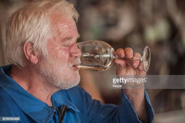 Senior Man with Beard Drinking White Wine