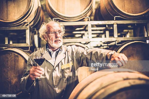 Uomo anziano con barba con un bicchiere di vino rosso