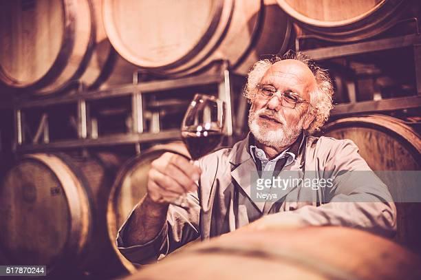 Alter Mann mit Bart und hält ein Glas Rotwein