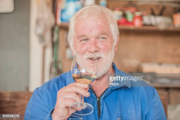 Senior Man with Beard Holding Glass of White Wine