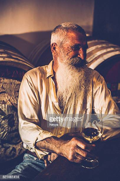 Senior homme avec barbe tenant un verre de vin dans la cave à vins