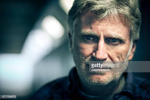 Hombre mayor con barba mirando a la cámara en un túnel subterráneo