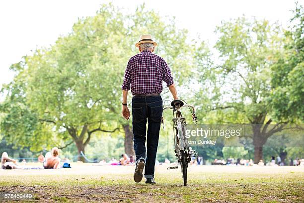 Senior man with bicycle in park, Hackney, London