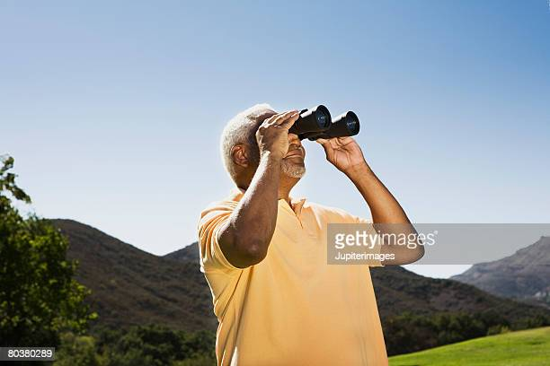 Senior man with binoculars