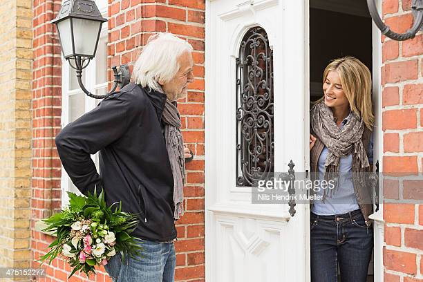 Senior man with bouquet, mid adult woman opening front door