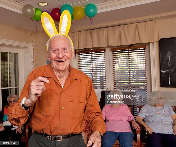 Senior man with bunny ears on dancing at party