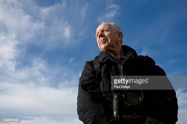 Senior man with camera wearing jacket