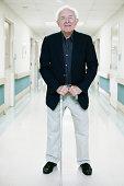 Senior man with cane standing in hospital corridor, portrait