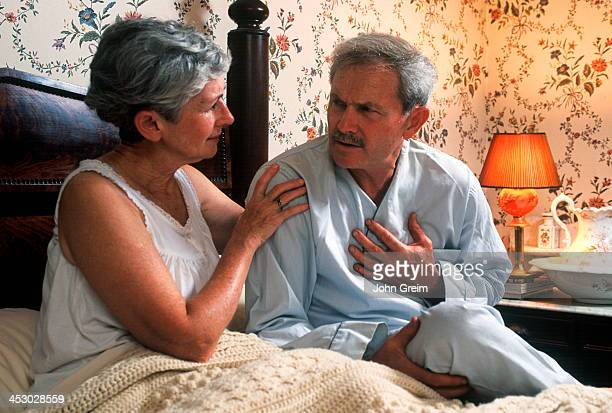 Senior man with chest pain is comforted by his concerned wife