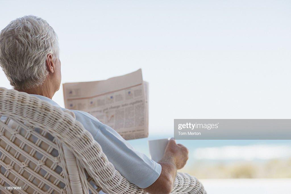 Senior man with coffee and newspaper on beach patio : Stock Photo