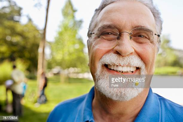 Senior Man with Daisy in Mouth