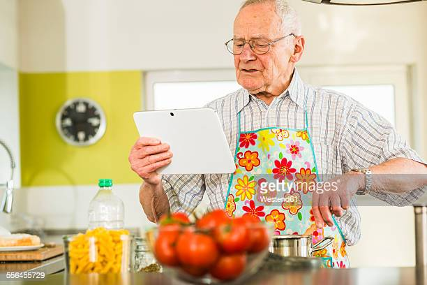 Senior man with digital tablet cooking in kitchen