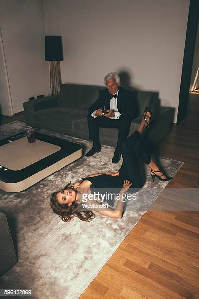 Senior man with drink on sofa looking at young woman lying on carpet
