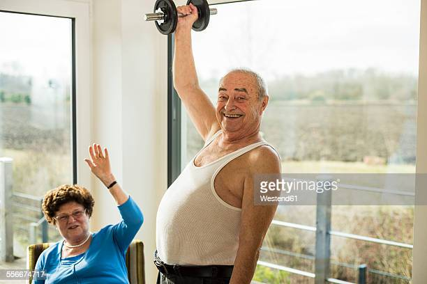 Senior man with dumbbell at home