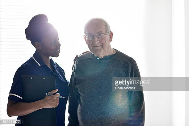 Senior man with female nurse at care home