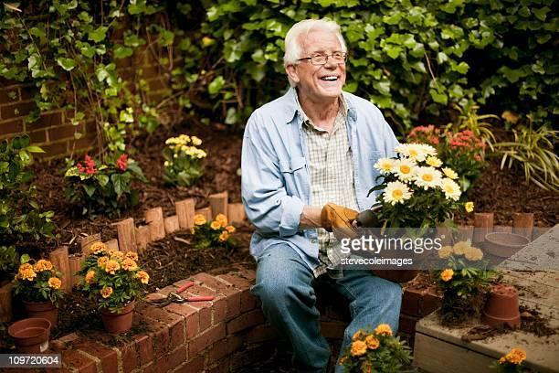 Senior Man with Flowers in Garden