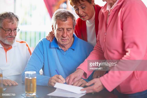 Senior man with friends signing document