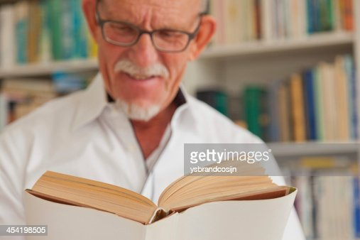 Senior man with glasses reading book in front of bookcase. : Stock Photo