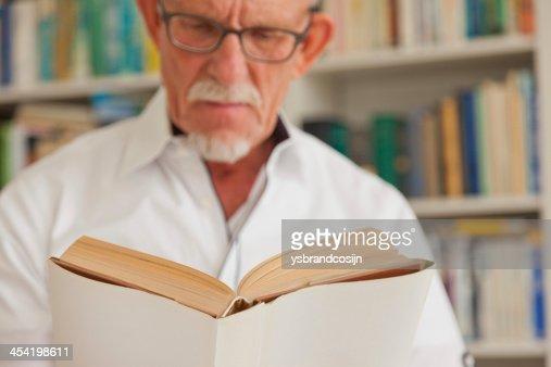 Hombre mayor leyendo libro con gafas en frente de bookcase. : Foto de stock