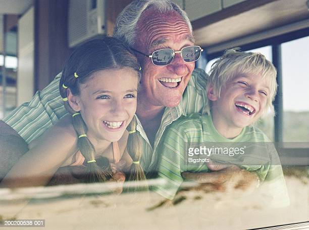Senior man with grandchildren (7-10) looking out window, laughing