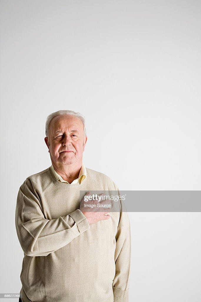Senior man with hand on heart : Stock Photo