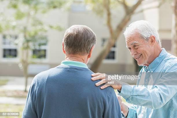 Uomo anziano con la mano sul suo amico sulla spalla