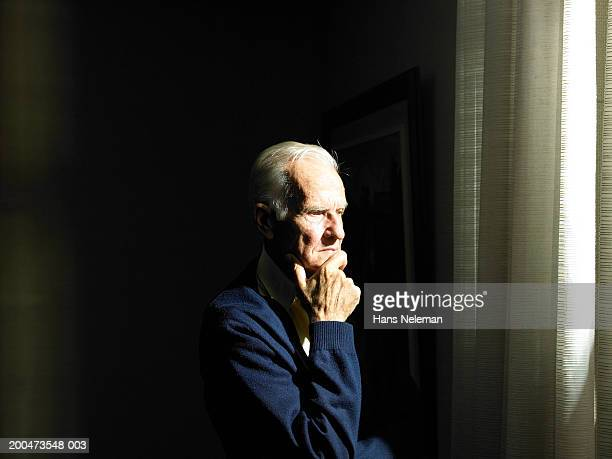 Senior man with hand to chin looking out window
