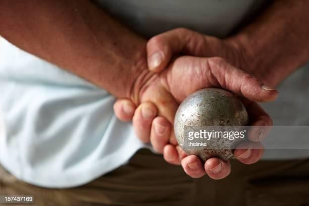 Senior man with hands behind his back holding a metal ball