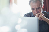 Senior man with hands clasped using laptop