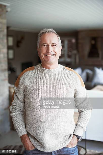 Senior man with hands in pockets standing at home