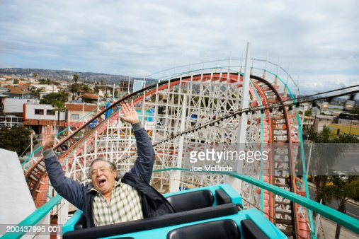 Senior man with hands raised, riding rollercoaster