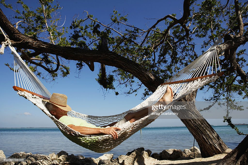 Senior man with hat on face sleeping in hammock, side view : Stock Photo