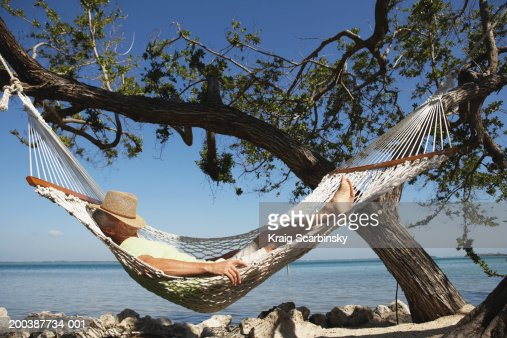 Senior Man With Hat On Face Sleeping In Hammock Side View