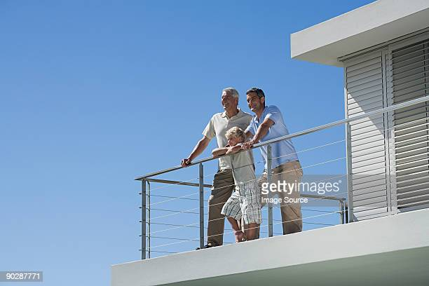 Senior man with his son and grandson looking at view from balcony