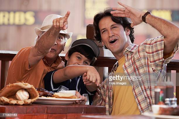 Senior man with his son and grandson pointing forward and smiling