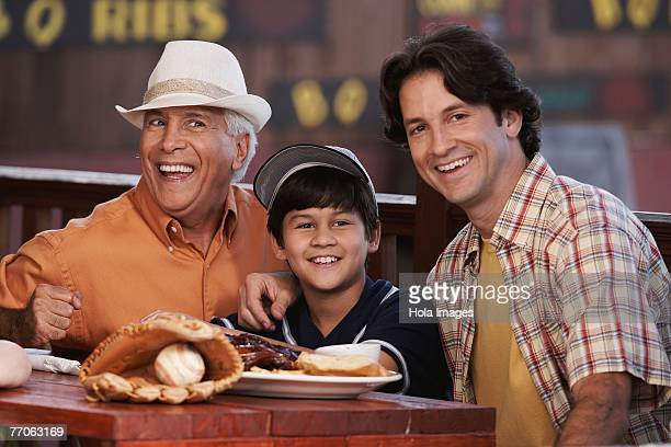 Senior man with his son and grandson sitting in a restaurant and smiling
