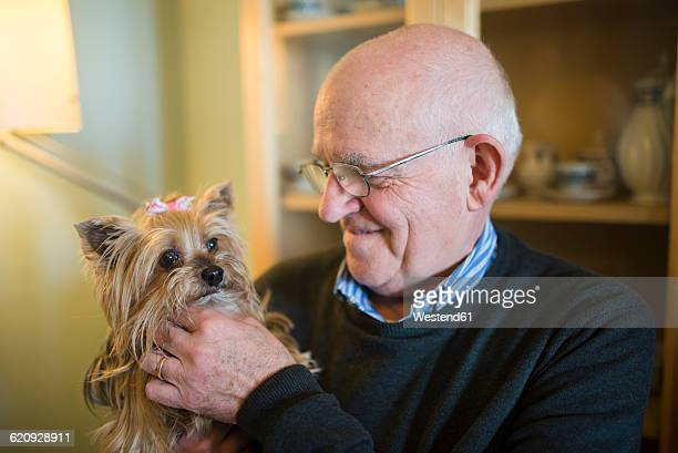Senior man with his Yorkshire terrier at home