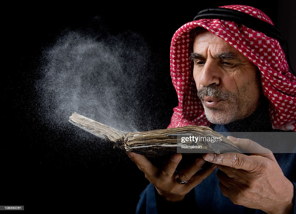Senior man with kaffiyeh blowing dust over old antique book : Stock Photo