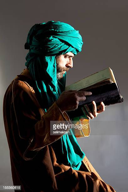 Senior man with kaffiyeh blowing dust over old antique book