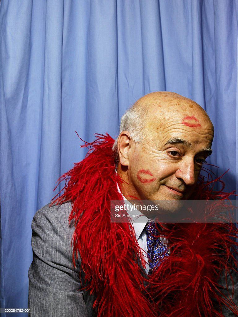 Senior man with kiss marks on face and head in phone booth : Stock Photo