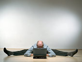 Senior man with legs stretched outward on floor using laptop