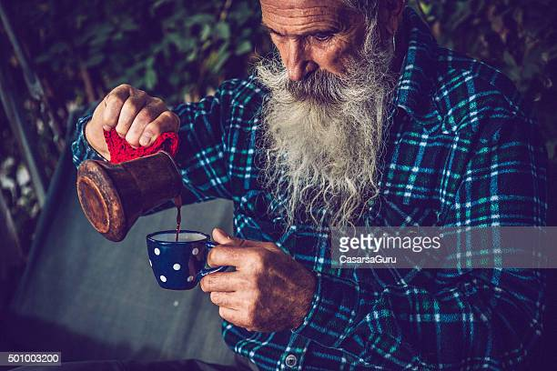 Senior Man with Long Beard Pouring Coffee Outdoors