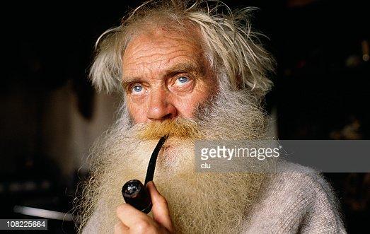 Senior Man With Long Beard Smoking Pipe