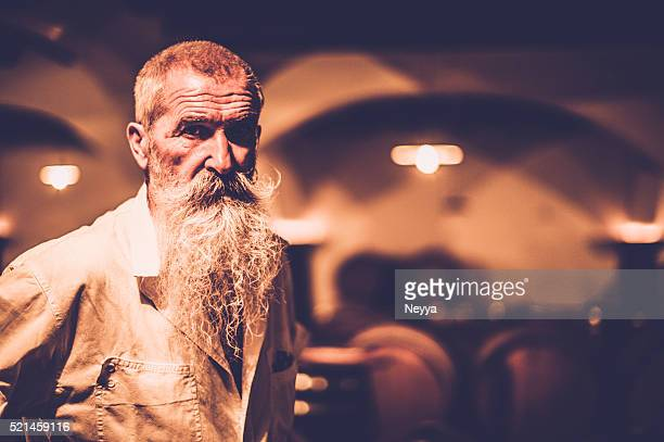 Senior Man with long Beard Standing in a Wine Store
