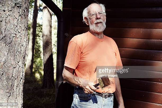 Senior man with paintbrush in front of wooden building