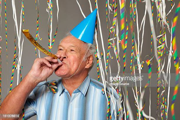 Senior man with party blower and streamers
