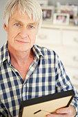 Senior man with photographs at home